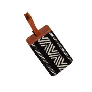 Global Goods Partners brand luggage tag in black with white zig zag embroidery, finished with a sturdy leather trim