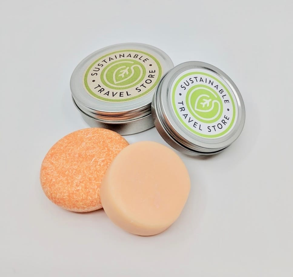 Pink Maverick brand solid shampoo and conditioner bars with tangerine and lemon scent; each bar comes with its own reusable travel tin
