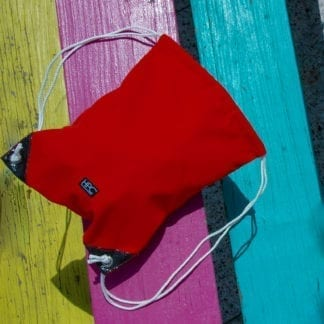 Hamilton Perkins brand recycled plastic red drawstring bag resting on a colorful picnic table.