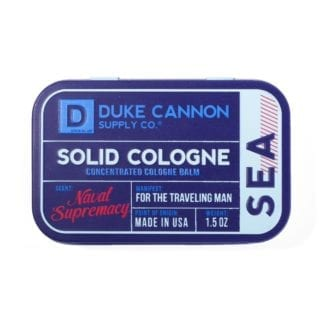 Duke Cannon brand environmentally friendly solid cologne in Sea - Naval Supremacy scent stored in metal tin.