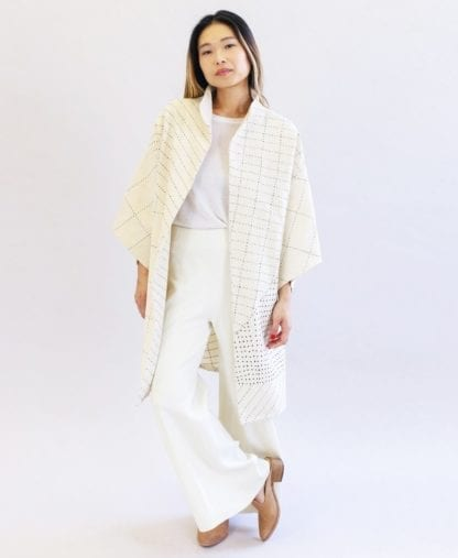 Woman wearing a sustainable handmade long kimono canvas jacket in bone white made by Anchal brand.