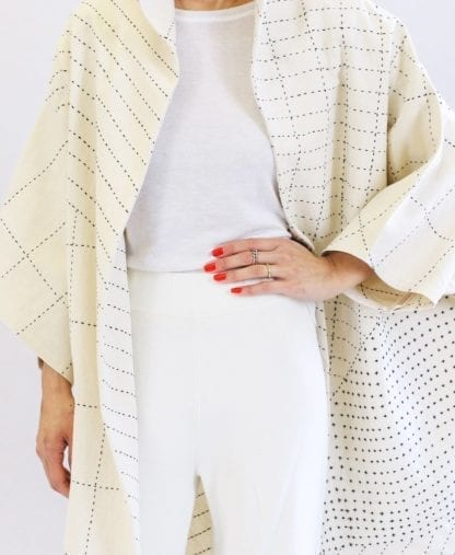 Close up of woman wearing a sustainable handmade long kimono canvas jacket in bone white made by Anchal brand.