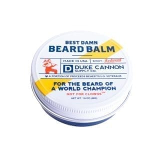 Duke Cannon brand eco friendly Best Damn Beard Balm Redwood scent in metal tin with top view display.