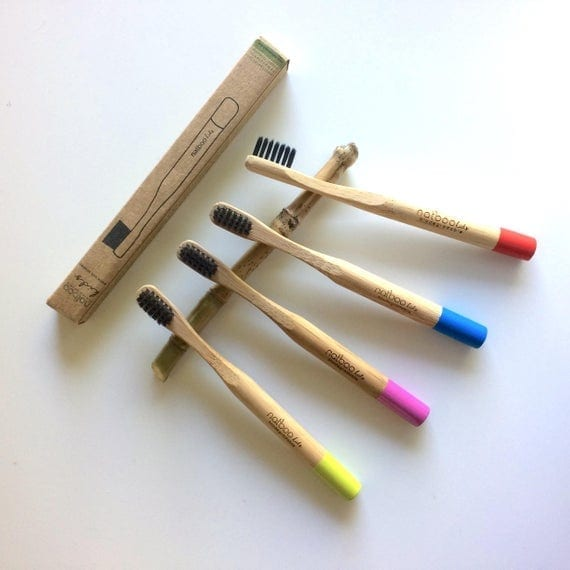 Earth friendly Natboo brand biodegradable bamboo toothbrush family set displayed resting on top of bamboo stick Natboo brand sustainable travel packaging.  Sold together as family set.