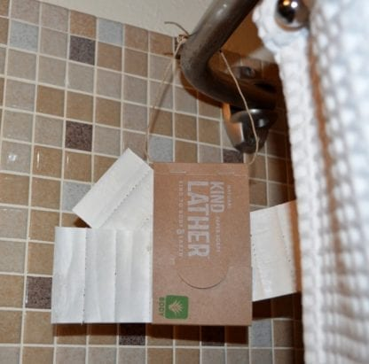 20 pack of KindLather brand Plant-based biodegradable unscented paper soaps for hands, body and shave in recycled paper packaging hanging on shower curtain rod.