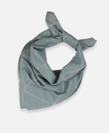 Product display of reusable green fair trade organic cotton bandana loosely tied, made by Anchal brand in spruce color with graph pattern.