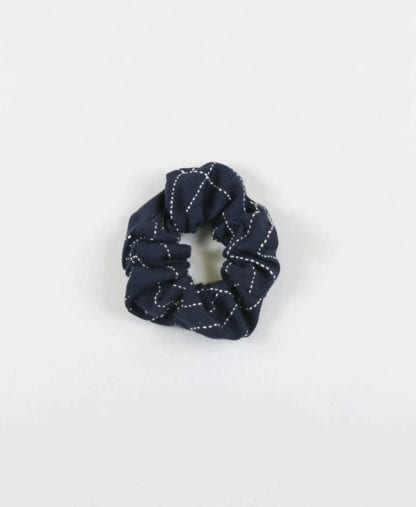 Overhead product display of environmentally friendly fair trade organic cotton Anchal brand scrunchie navy color.