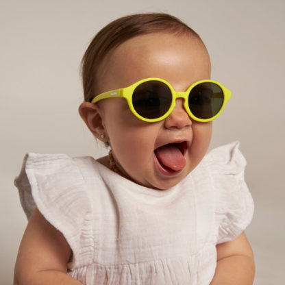 Baby girl in sustainable recycled rubber kids Parafina Tortuga sunglasses in yellow