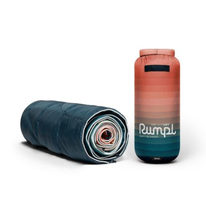 The eco-friendly Nanoloft puffy blanket in patina pixel fade has a navy backing and a white binding. Its stuff sack has about 15 faded colors from pink to blue on the exterior.